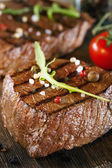 Close up of two juicy thick portions of delicious roasted or grilled beef steak — Stock Photo