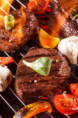 Beef steak on a barbecue grill with flames with vegetables — Stock Photo