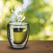 Hot green tea on wood table with outdoor background — Stock Photo