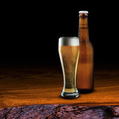 Bottle and glass of cold beer on wood table — Stock Photo