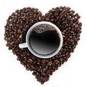 A cup of coffee in the center of the coffee beans forming a heart shape — Stock Photo