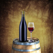 Red wine bottle and glass on wood barrel — Stock Photo