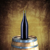 Red wine bottle on wood barrel — Stock Photo