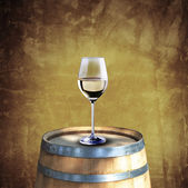 White wine glass on wood barrel — Stock Photo