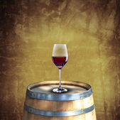 Red wine glass on wood barrel — Stock Photo