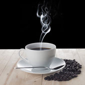 Hot cup of coffee and coffee beans on wood table — Stock Photo