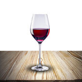 Glass of red wine on wood table — Stock Photo