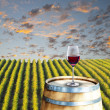 Glass of red wine on wood barrel — Stock Photo