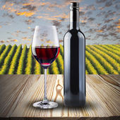 Glass and bottle of red wine on wood table — Stock Photo