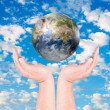 Man's hands holding on globe on cloudy blue sky — Stock Photo