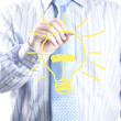Businessman with a pen in hand drawing light bulb — Stock Photo