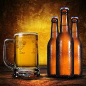 Jug of beer and three beer bottles — Stock Photo