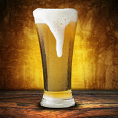 Beer in glass with foam spills — Stock Photo
