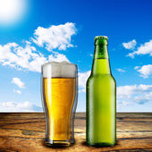 Glass of beer and beer bottle — Stock Photo