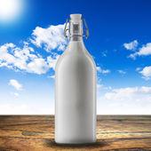 Milk bottle on green grass — Stock Photo