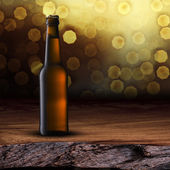 Beer bottle on wood table — Stock Photo
