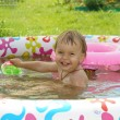 Two-year-old girl bathes in inflatable paddling pool and laughs — Stock Photo