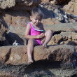 Two-year-old girl in a pink bathing suit sitting on stones and s — Stock Photo #37184161