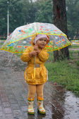 Two-year-old girl in a yellow raincoat hiding from the rain unde — Stock Photo