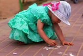 Two-year-old girl draws a chalk on the street — Stock Photo