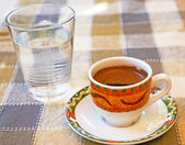 Strong Cypriot coffee with water water in a glass — Stock Photo