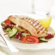 Grilled salmon steak served on letuce tomato and cucumber — Stock Photo