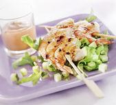 Grillowane krewetki na szpikulec podawane na talerzu z sałatką — Zdjęcie stockowe