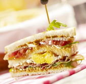 Sandwich with three layers, filled with bacon eggs and lettuce — Stock Photo