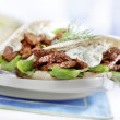 Pita with gyros served on a plate with lettuce — Stock Photo #29442465