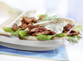 Pita with gyros served on a plate with lettuce — Stock Photo