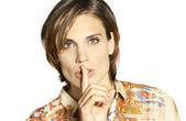 Beautiful woman with her finger on her lips — Stock Photo