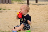 Ragazzo in una sandbox con un giocattolo — Foto Stock