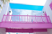Pink wooden bridge with white mediterranean building — Stock Photo