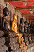 The sitting golden Buddha stute and Black stute in ancient templ — Photo
