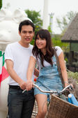 Portrait of a happy couple smiling at camera with bicycle — Foto de Stock
