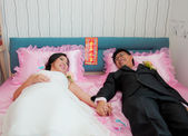 Bride and groom hold their hand and lay on the bed as Chinese Tr — Stock Photo