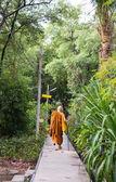 Um monge asiático caminha na passarela — Fotografia Stock