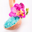 Spa salt in wooden spoon with beautiful pink Freesia flower. — Stock Photo