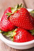 Nahaufnahme der erdbeeren in weißer teller auf holztisch. — Stockfoto