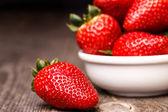 Erdbeeren in weißer teller auf dem alten holztisch. — Stockfoto