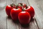 Fresh tomatoes on the old wooden board. — Stock Photo