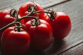 Nahaufnahme der frische tomaten auf dem alten holzbrett. — Stockfoto