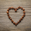 Heart shape made from coffee beans on wooden table. — Stock Photo