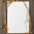 White paper on wooden surface with golden bow above. — Stock Photo