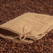 Coffee bag on coffee beans surface. Focused on bow. — Stock Photo