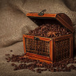 Old wooden treasure chest filled with coffee beans and anise stars . — Stock Photo