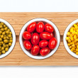 Corn, tomatoes and peas in white plates on wooden stand. — Stock Photo