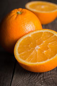 Close-up of orange fruit on wooden board. Focused on the middle of the front orange — Stock Photo