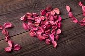 Miłość tytuł wykonane z różowego potpourri na drewniane tekstury — Zdjęcie stockowe