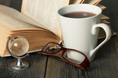Warm tea cup on wooden table with old book, glasses and glass globe. — Stock Photo